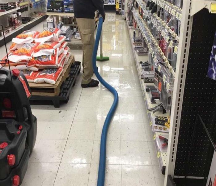 technician vacuuming up the standing water same location in the store