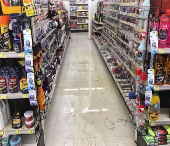 standing wall in aisle of auto store showing shelves with merchandise