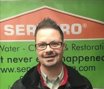 Male office employee in front of a SERVPRO banner