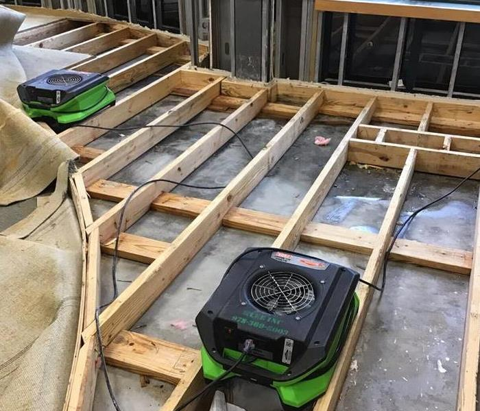 SERVPRO drying equipment siting on open floor beams.
