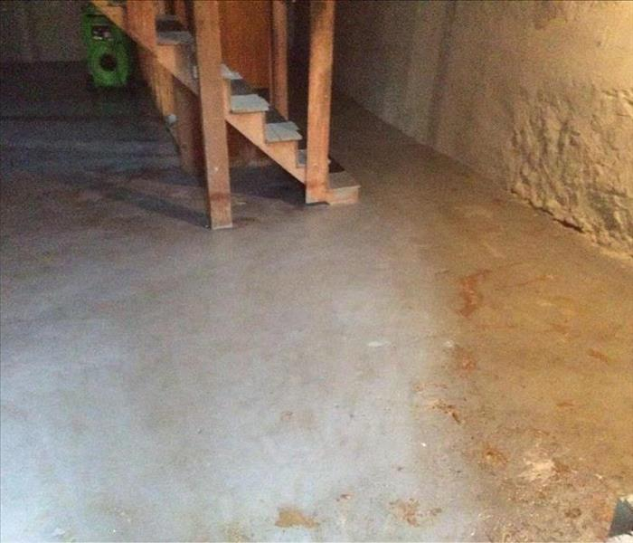 Cleaned concrete basement, walls, and showing steps leading down
