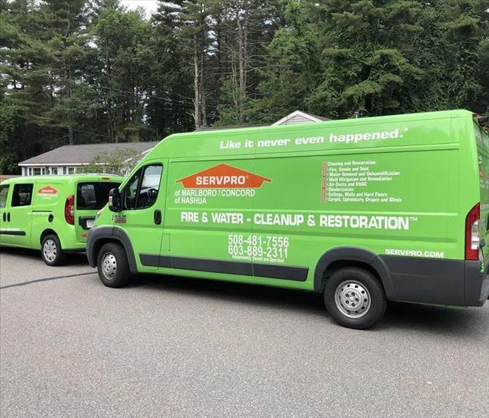 Two SERVPRO vehicles parked in front of a home.
