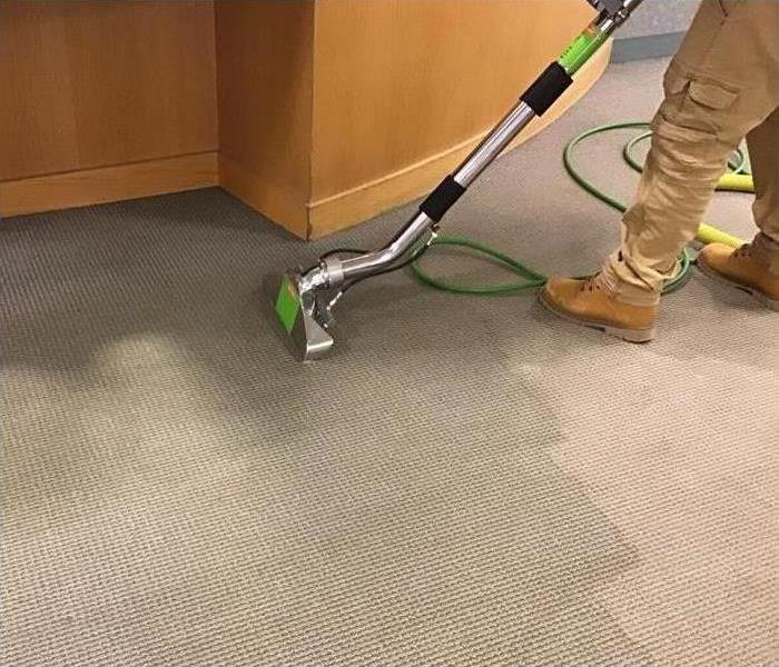A technician using a cleaning device on the carpet in this building